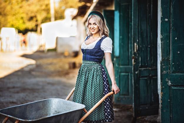 Hübsche lächelnde blondine im traditionellen kleid mit schubkarre, die im hinterhof arbeitet.