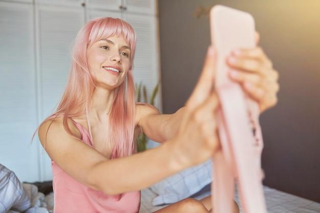 Hübsche lächelnde dame im eleganten pyjama macht selfie mit handy im schlafzimmer