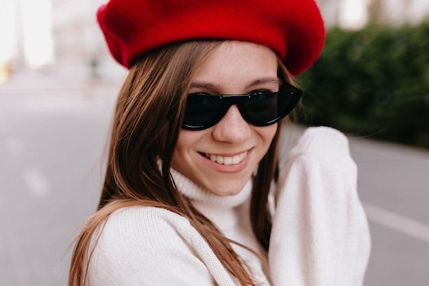 Hübsche lächelnde dame in roter baskenmütze und schwarzer brille hat eine gute zeit im herbstwochenende