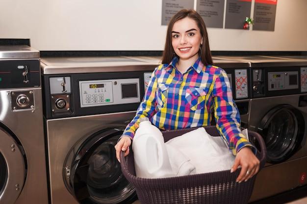 Hübsche lächelnde frau am waschsalon hält einen korb mit kleidern.
