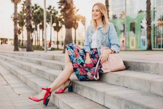 Hübsche lächelnde frau, die auf treppen in der stadtstraße im stilvollen bedruckten rock und in der übergroßen jeansjacke mit lederrucksack, sommerarttrend sitzt