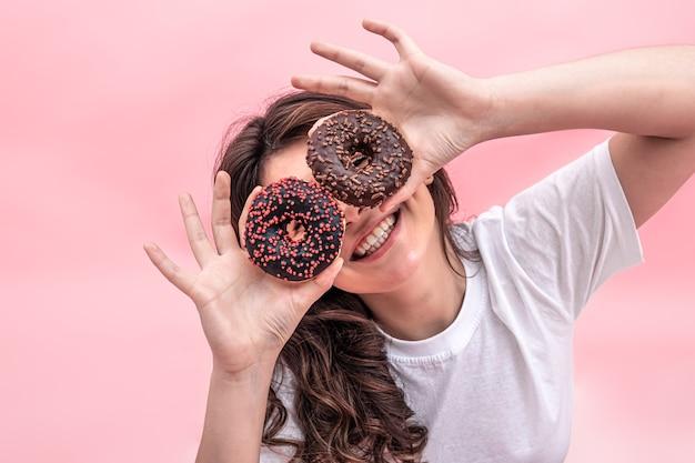 Hübsche lächelnde frau, die donuts in ihren händen auf einem rosa hintergrund hält
