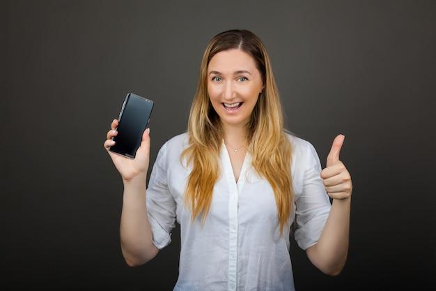 Hübsche lächelnde frau, die einen leeren vertikalen smartphonebildschirm zeigt