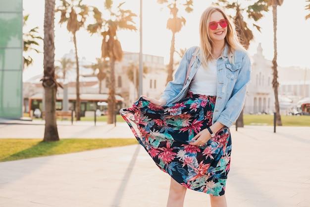 Hübsche lächelnde frau, die in der stadtstraße im stilvollen bedruckten rock und in der übergroßen jeansjacke trägt, die rosa sonnenbrille, sommerarttrend trägt