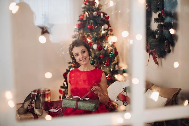 Hübsche lächelnde frau, die in ihrem schlafzimmer mit weihnachtsgeschenk sitzt
