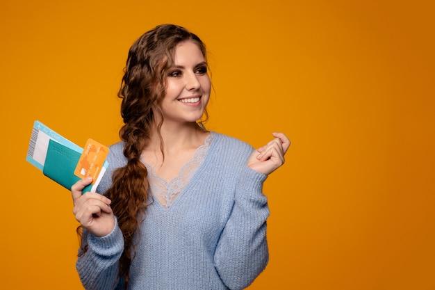 Hübsche lächelnde frau, die tickets online per kreditkarte kauft