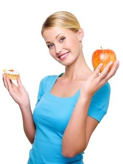 Hübsche lächelnde frau wählen aus süßem kuchen und frischem apfel
