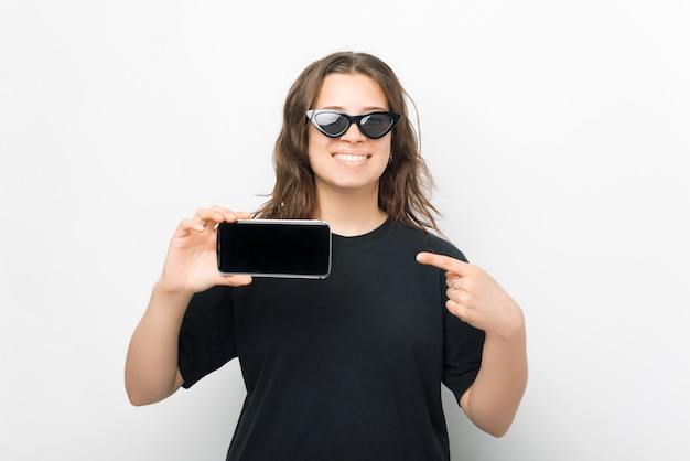 Hübsche lächelnde frau zeigt auf den bildschirm des telefons, das sie hält.