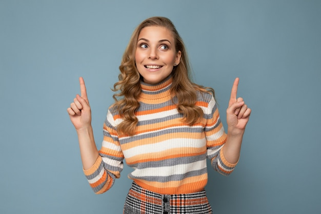 Hübsche lächelnde glückliche junge frau, die mit dem finger auf exemplar zeigt