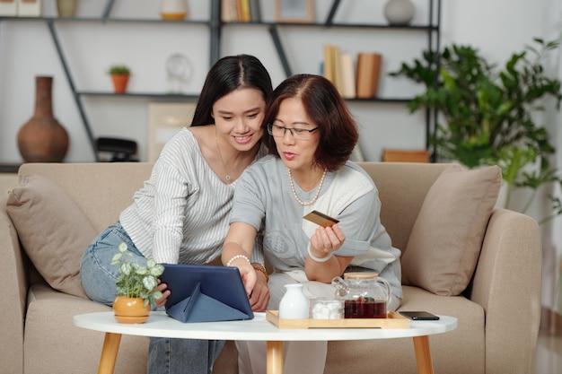 Hübsche lächelnde junge asiatin, die mutter hilft, online einzukaufen und einkäufe zu bezahlen, wenn sie auf dem sofa im wohnzimmer sitzt und tee trinkt