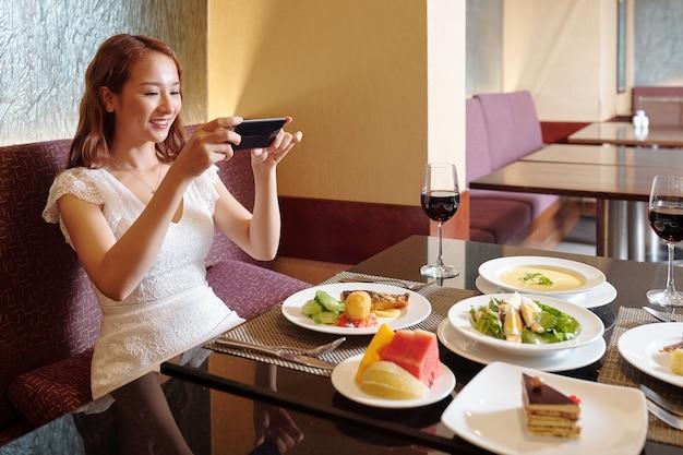 Hübsche lächelnde junge frau, die einen restauranttisch mit verschiedenen gerichten für soziale medien fotografiert