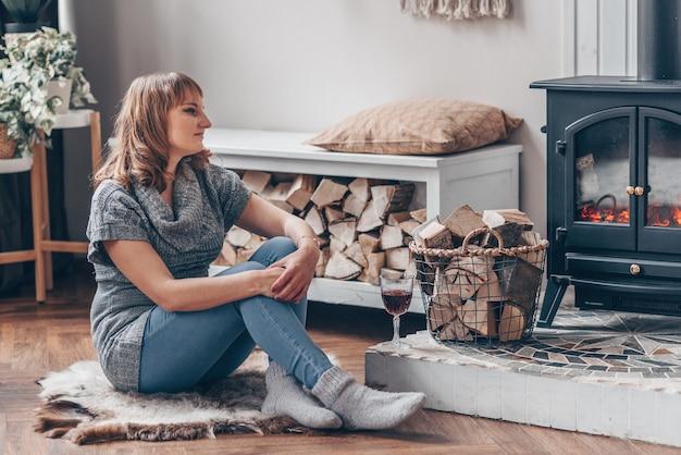 Hübsche lächelnde junge frau sitzt in der nähe des lagerfeuers im herbst oder im waldhaus. winter entspannungskonzept.