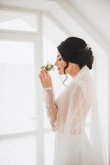 Hübsche lächelnde kaukasische braut, die einen zarten knopflochblumenstrauß riecht