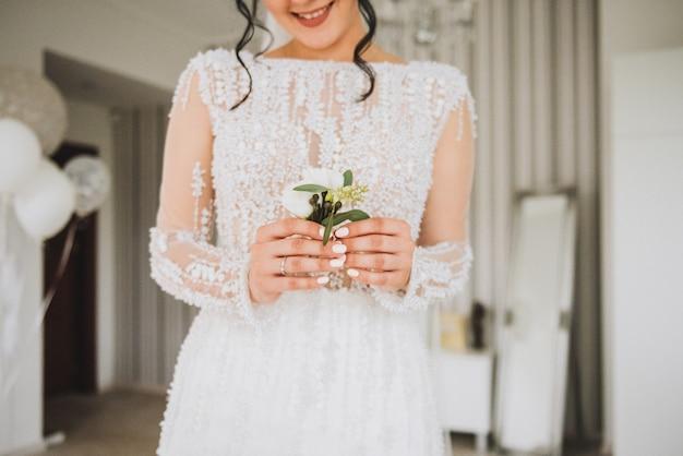 Hübsche lächelnde kaukasische braut mit einem zarten knopflochblumenstrauß