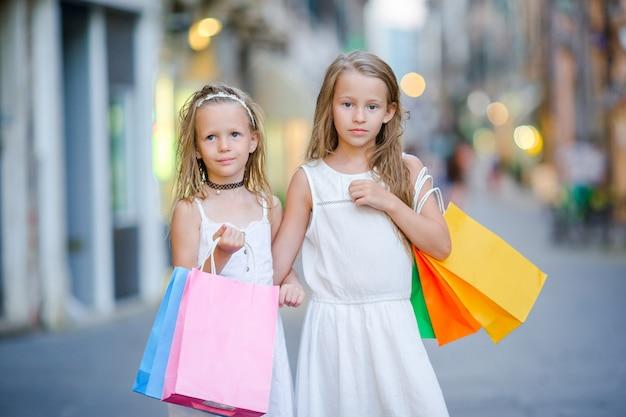 Hübsche lächelnde kleine mädchen mit einkaufstüten