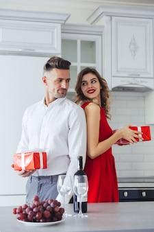 Hübsche lächelnde liebhaber, die einander zu hause geschenk geben, valentinstagkonzept