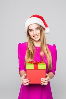 Hübsche lächelnde lustige glückliche dame im kurzen rosa kleid und im neujahrshut halten papierboxüberraschung in ihren händen
