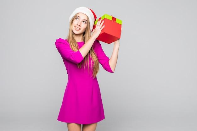 Hübsche lächelnde lustige glückliche dame im kurzen rosa kleid und im neujahrshut halten papierkasten in ihren händen