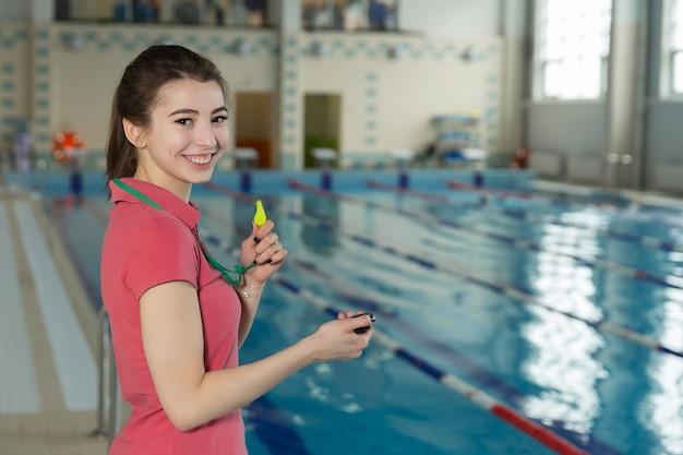 Hübsche lächelnde trainerfrau, die eine stoppuhr am pool hält.