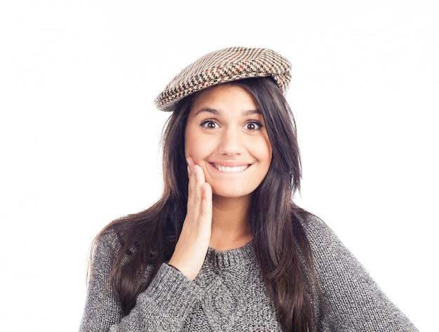 Hübsche lächelnde und nette brunettefrau mit einer französischen kappe und einer wollstrickjacke
