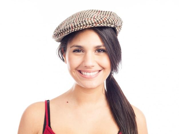 Hübsche lächelnde und nette brunettefrau mit französischer kappe und rotem trägershirt