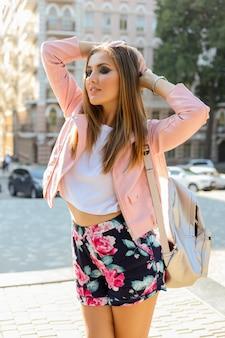 Hübsche lange frau, die auf der straße aufwirft. tragen sie eine stilvolle sonnenbrille, eine rosa lederjacke und einen rucksack.