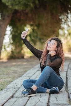 Hübsche lateinamerikanische frau mit brille, die ein selbstporträt mit ihrem smarphone tut, das auf einem hölzernen weg im feld draußen sitzt