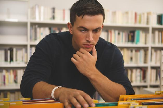 Hübsche lesung des jungen mannes an der bibliothek