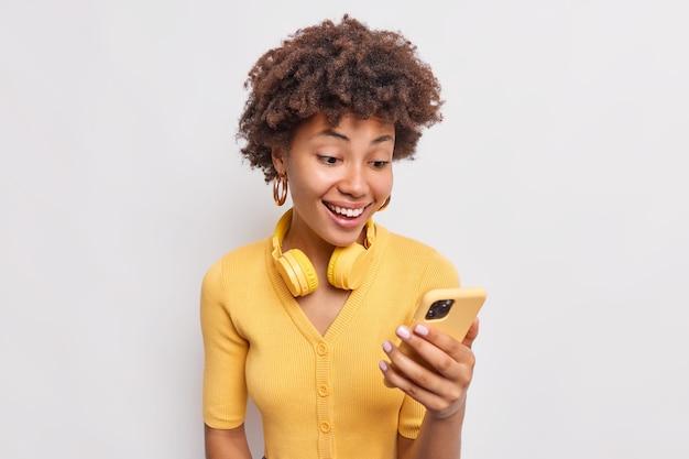 Hübsche lockige frau chattet auf dem handy lächelt angenehm lädt songs in der playlist herunter trägt kopfhörer um den hals, die mit dem drahtlosen internet verbunden sind, gekleidet in gelben pullover posen drinnen