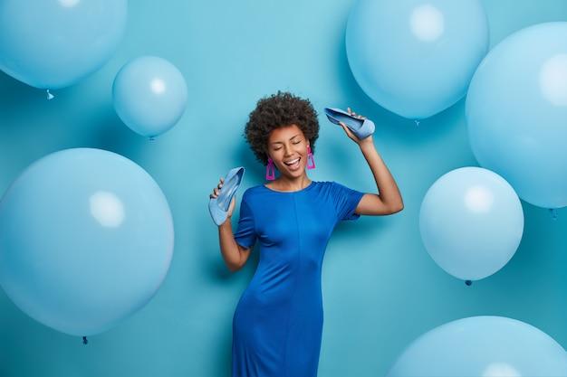 Hübsche lockige frau chillt auf der party, tanzt glücklich, hält die hände mit schuhen hoch, verbringt zeit im nachtclub, zieht schuhe mit hohen absätzen aus und posiert an der blauen wand. monochromer schuss. urlaub, feier
