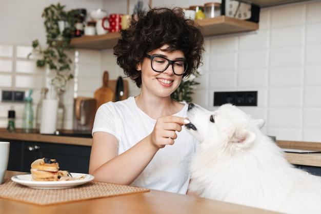 Hübsche lockige frau, die an der küche sitzt, essen kuchen und füttert ihren süßen weißen hund