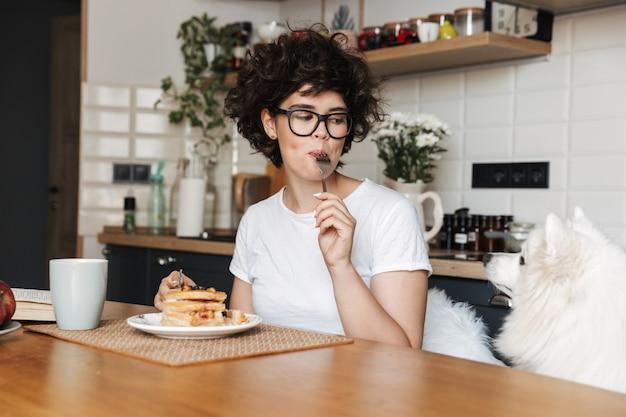 Hübsche lockige frau, die an der küche sitzt und tee trinkt, kuchen isst
