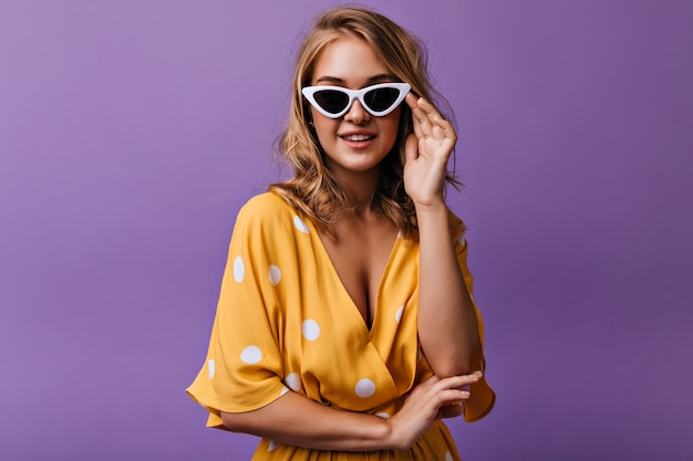 Hübsche lockige frau in der dunklen sonnenbrille, die aufwirft. sinnliches weibliches modell in der gelben bluse, die auf purpur steht.