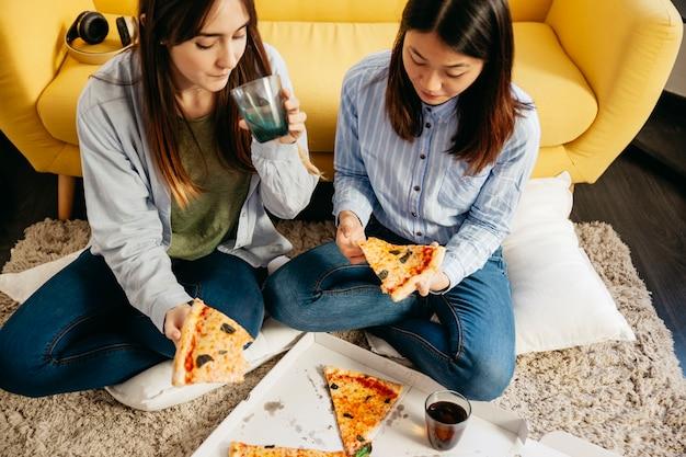 Hübsche mädchen, die pizza auf boden haben