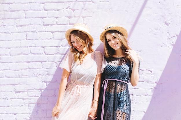 Hübsche mädchen in stilvollen sommerkleidern posieren zusammen, nachdem sie durch die stadt gelaufen sind und gelächelt haben