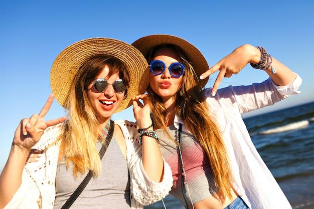 Hübsche mädchen machen selfie und senden luftküsse an die kamera, sommerreisezeit, boho kleidung sonnenbrille und strohhüte.