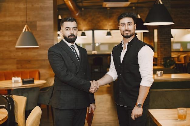 Hübsche männer in einem restaurant, händeschütteln