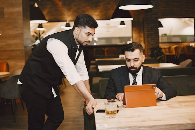 Hübsche männer in schwarzen anzügen, die in einem café arbeiten