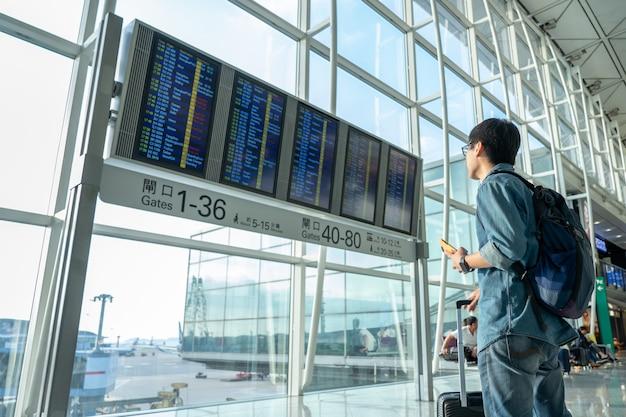 Hübsche männliche touristen benutzen smartphones, um flüge vor dem einsteigen zu überprüfen.