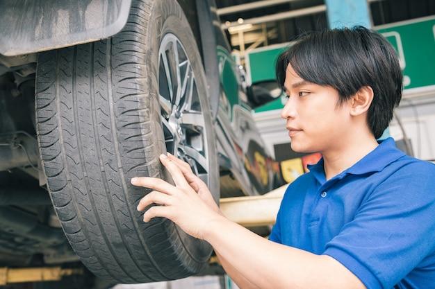 Hübsche mechaniker in uniform arbeiten im auto-service mit leichtmetallrad.