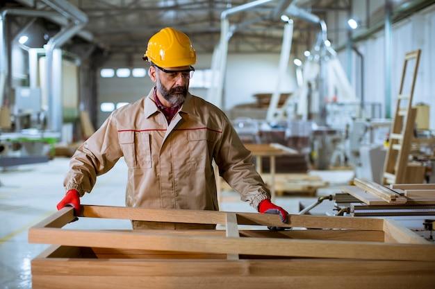 Hübsche mittlere gealterte arbeitskraft, die in der möbelfabrik arbeitet