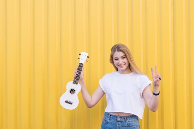 Hübsche modelblondine mit einer weißen ukulele in ihren händen posiert auf einer gelben wand.