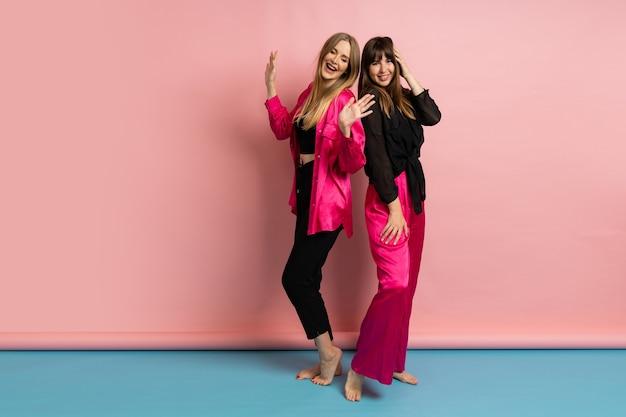 Hübsche modische frauen, die ein stilvolles buntes outfit tragen und an einer rosa wand posieren