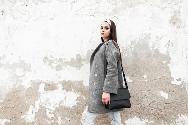 Hübsche modische junge frau mit stilvoller schwarzer tasche im trendigen grauen mantel mit glamour-bandana ruht in der nähe der weißen vintage-wand im freien. reizendes mädchen in der modefrühlingsjugendkleidung, die in der straße aufwirft.
