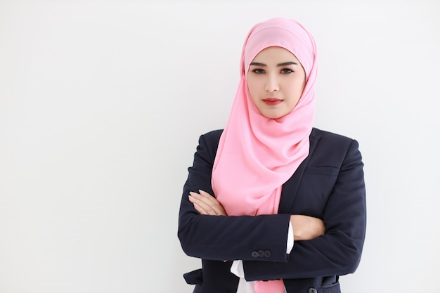 Hübsche muslimische junge asiatische frau, die blauen anzug trägt, der zuversichtlich lächelt