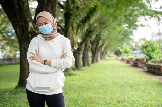 Hübsche muslimische sportlerin mit gesichtsmaske, die kamera während der übung im freien betrachtet