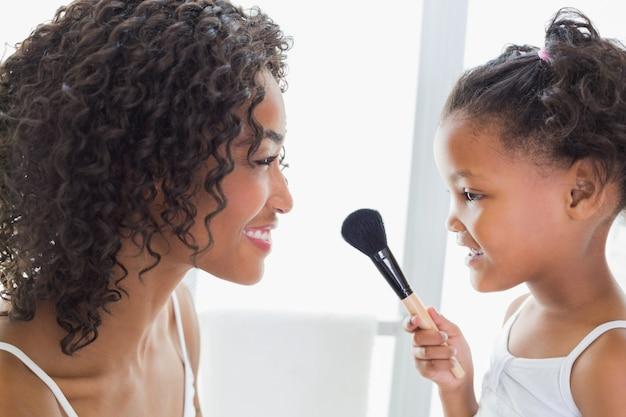 Hübsche mutter, die ihre tochter über make-up unterrichtet