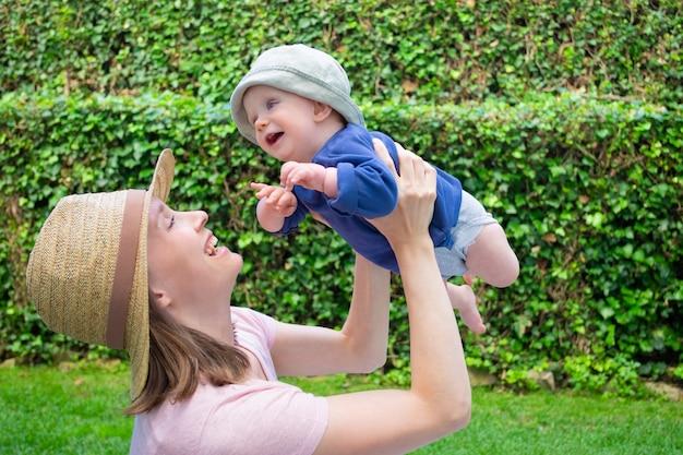 Hübsche mutter, die mit tochter im park spielt und lächelt. nettes baby in blauem hemd und hut, die weg mit offenem mund schauen
