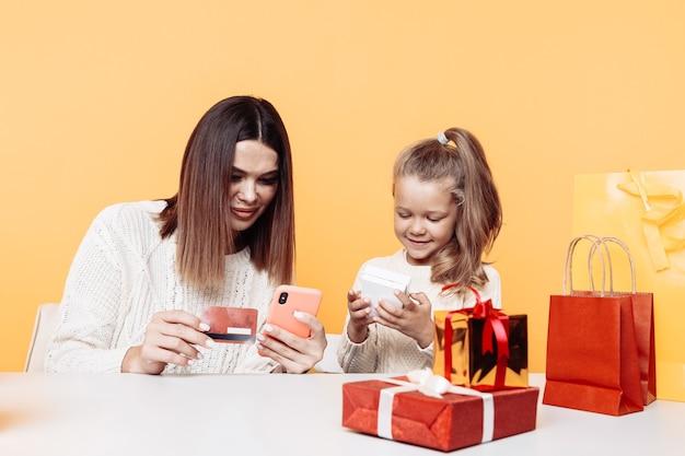 Hübsche mutter mit kleiner tochter, die mit geschenken am schreibtisch sitzt und telefon verwendet, um geschenke online auszuwählen.