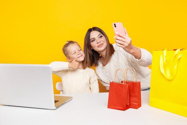 Hübsche mutter und süße tochter machen selfie am telefon zusammen im gelben studio.